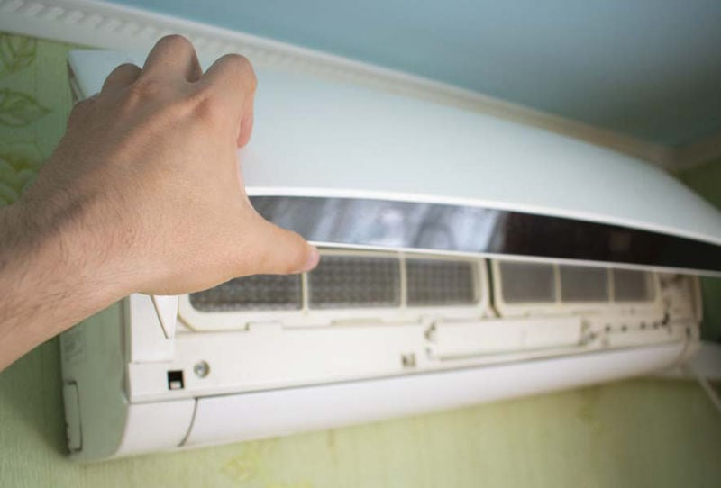 hand open the lid of the air conditioner in the room