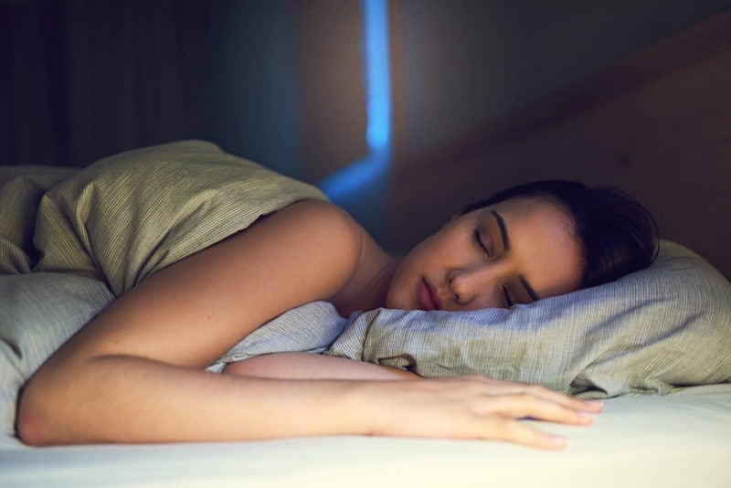 Shot of a young woman sound asleep in her bedroom ac sleeping benefits