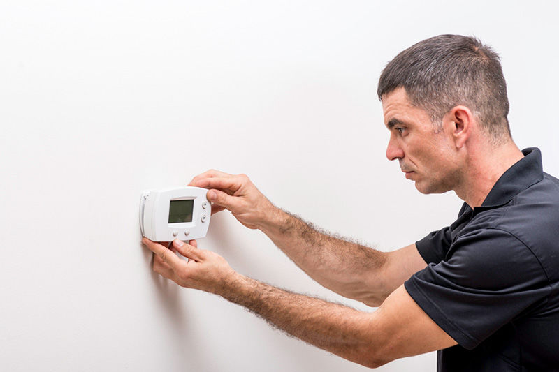Man fixing a Thermostat